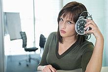 Porträt einer Geschäftsfrau mit einem Wecker