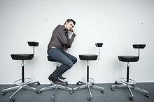 Geschäftsmann auf einem Stuhl sitzend und nachdenkend