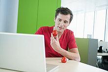 Geschäftsmann mit Tomate und Laptop