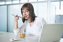 Geschäftsfrau beim Nudelessen vor dem Laptop