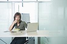 Geschäftsfrau, die Bohnensprossen isst und einen Laptop benutzt.