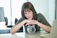 Porträt einer Geschäftsfrau, die sich auf einen Wecker stützt