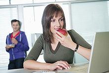 Geschäftsfrau, die einen Apfel isst und einen Laptop benutzt