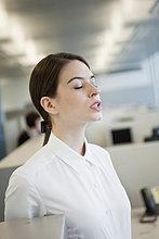 Geschäftsfrau, die mit geschlossenen Augen in einem Büro steht.