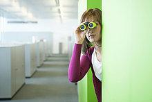 Geschäftsfrau beim Durchschauen eines Fernglases in einem Büroflur