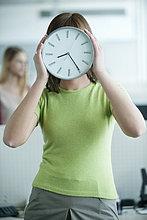 Geschäftsfrau mit einer Uhr vor dem Gesicht