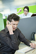 Geschäftsleute sprechen auf dem Handy, während sein Kollege wütend aussieht.