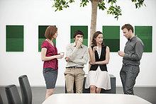 Geschäftsleute im Gespräch in einem Konferenzraum während einer Kaffeepause