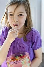 Porträt eines Mädchens, das Kaugummidrops isst