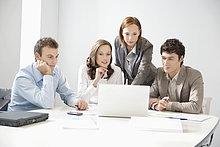 Geschäftsleute betrachten einen Laptop in einem Vorstandszimmer