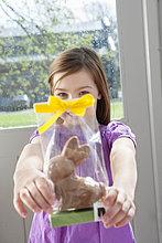 Porträt eines Mädchens mit einem Osterhasen vor dem Gesicht
