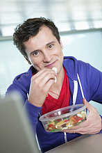 Geschäftsmann beim Essen von Kaugummidrops vor einem Laptop