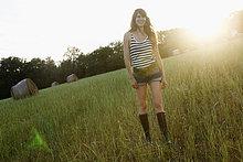 Lächelnde Frau beim Spaziergang im Grasfeld