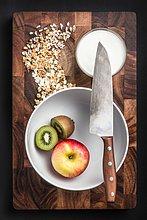 Stilleben von Apfel und Kiwi in Schale mit Joghurt und Hafer