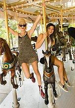 Zwei junge Frauen reiten Pferdekarussell im Park