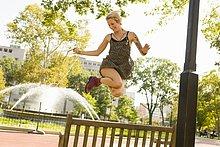 Junge Frau beim Springen in der Luft im Park