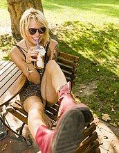 Porträt einer jungen Frau im Park, die Frappe trinkt.