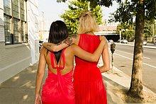 Rückansicht von zwei jungen Frauen in roten Kleidern, die auf der Straße spazieren gehen.