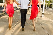 Rückansicht von zwei jungen Frauen Arm in Arm mit einem Freund, der auf der Straße spazieren geht.