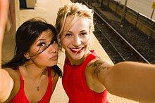 Zwei junge Frauen nehmen Selfie auf dem Bahnsteig.