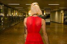 Rückansicht der jungen Frau in rotem Kleid in der U-Bahn-Station