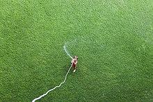 Kleiner Junge auf dem Rasen stehend mit Gartenschlauch, Draufsicht