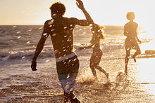 Verspielte Freunde am Strand bei Sonnenuntergang